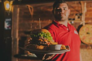 waiter holding plate with a burger